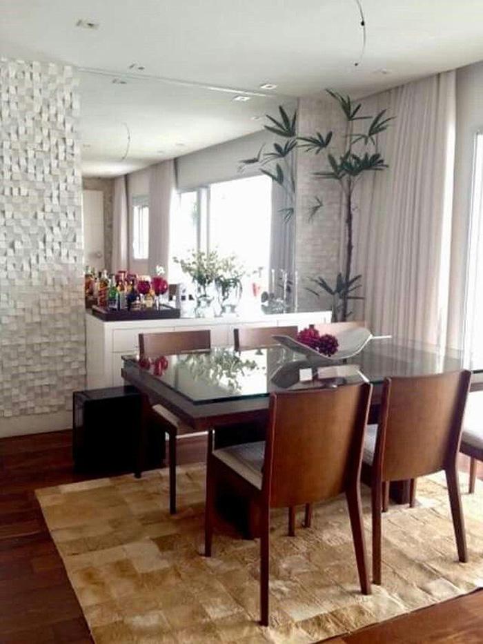 Büyük bir ayna ve 3D kaplama ile süslenmiş bir duvarlı yemek odası